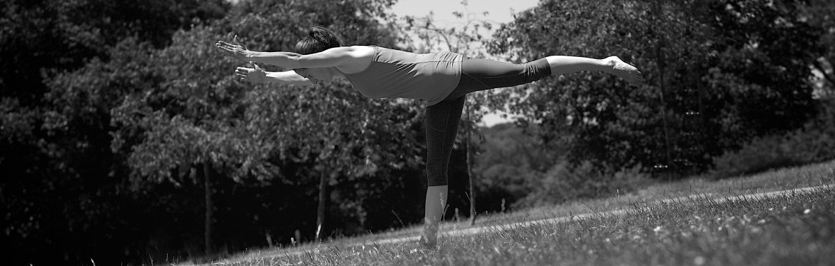 Laura doing a yoga pose in a park