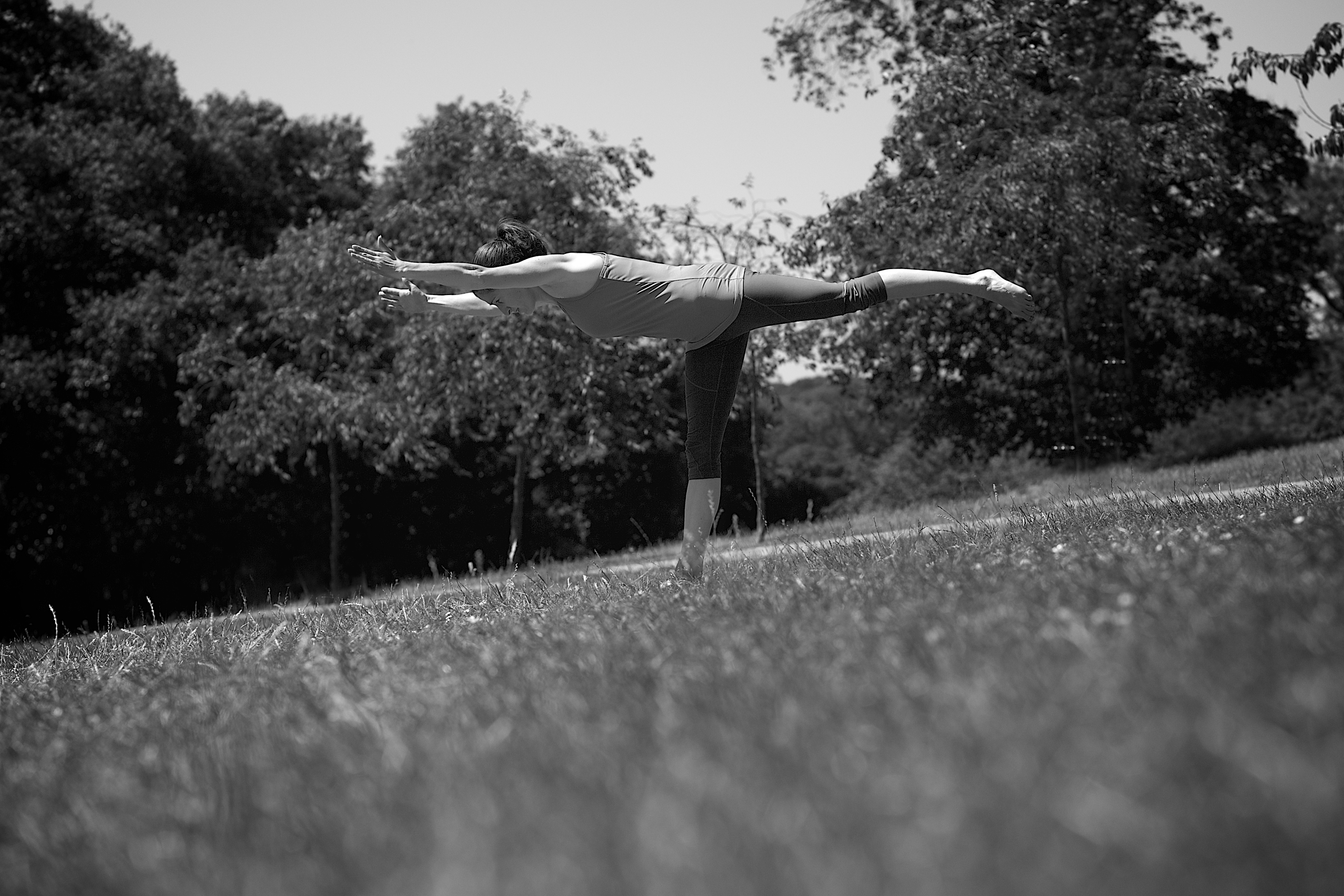 Laura doing a yoga pose in a park.